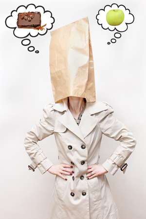 Woman with paper bag over her head thinking about sweets and healthy food photo