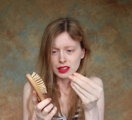 Young blonde women upset about losing her hair Stock Photo