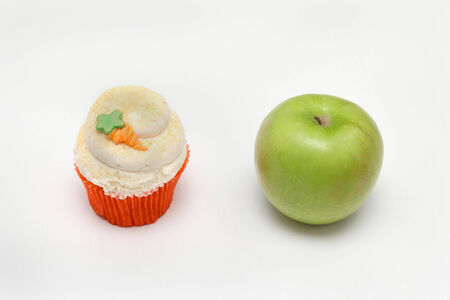 Cupcake and apple representing healthy and unhealthy food choices