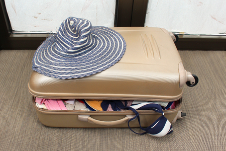 Overfilled suitcase with clothes packed for summer vacation photo