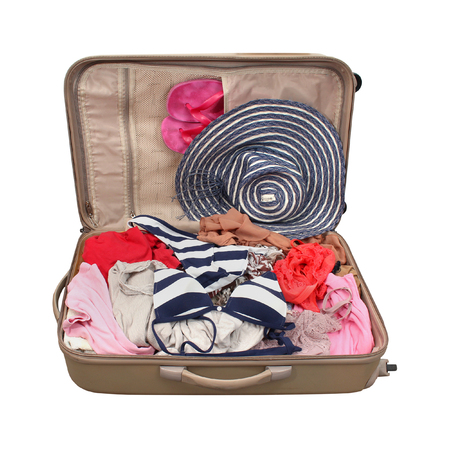 Open suitcase with summer vacation clothes isolated with clipping path included photo