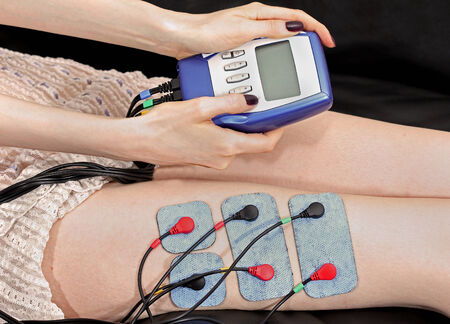 Woman using small electro stimulation device on her thigh Stock Photo