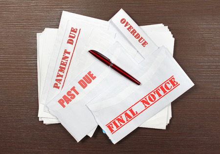bill payment: Pile of open envelopes with missed bill payment notices