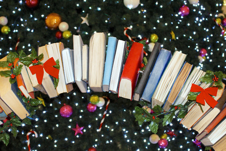 Books ornaments with red bows hanging from Christmas tree