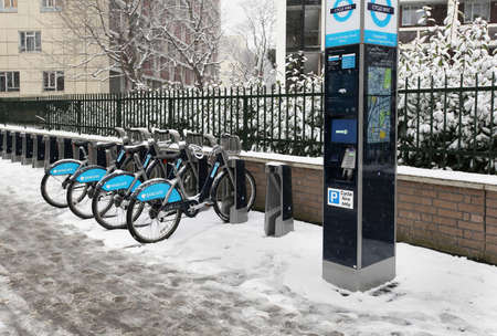 LONDON, UK - January 20; Cycle hire scheme founded by Boris Johnson mayor of London and Barclays in London, UK - January 20, 2013; Bicycles for hire on London sidewalk during winter season under snow