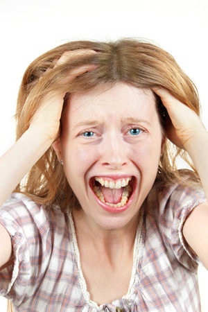 Young woman screaming in agony with mouth wide open holding head