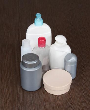 productos de aseo: Botellas de art�culos de tocador de pl�stico en el fondo de madera marr�n
