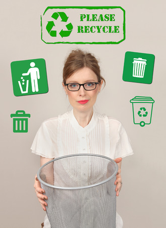 encouraging: Young woman holding empty silver trashcan encouraging people to recycle