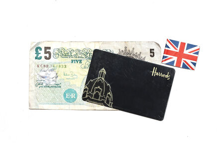 harrods: London, United Kingdom - July 28, 2014: Harrods department store loyalty card with five pounds bill and Union Jack flag illustrating British consumerism Editorial