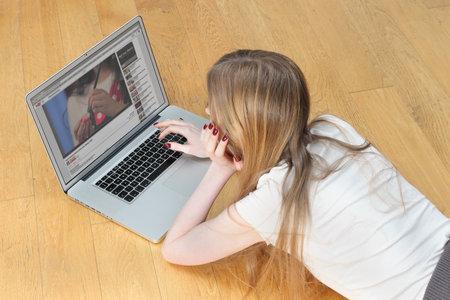 jeune fille adolescente: Belgrade, Serbie - le 27 Novembre, 2014: Adolescente pose sur le sol en face de l'ordinateur portable en regardant des vidéos YouTube recherche de faire en place des tutoriels Éditoriale