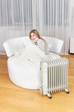 very cold: Young girl trying to keep warm at home next to electronic radiator and under blanket during very cold weather