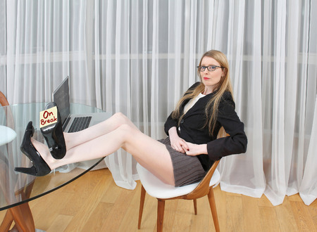 feet on desk: Young woman seating in the office with feet up on a table and on break post it note pasted to the shoe