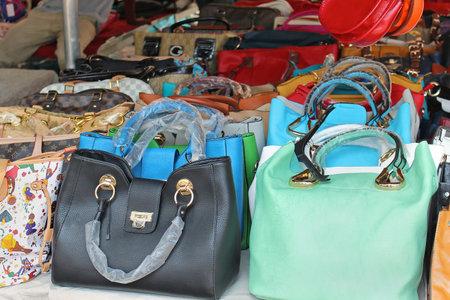ROM, ITALIEN - 29. Juni 2014: Großer Stapel der bunten gefälschte Handtaschen von bekannten Modemarken am Porta Portese Flohmarkt in Rom, Italien verkauft - 29. JUNI; Gefälschte Kopien der populären Mode-Handtaschen Standard-Bild - 34497640