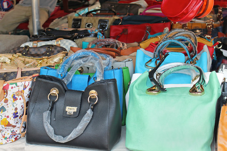ROME, ITALY - JUNE 29, 2014: Big pile of colorful counterfeit handbags of famous fashion brands sold on Porta Portese flea market in Rome, Italy - June 29; Fake copies of popular fashion handbags
