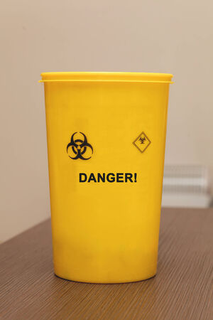 hazardous waste: Medical waste yellow plastic container for disposing needles and other hazardous objects