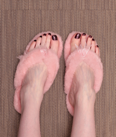 Female feet with bright nail polish in fluffy flip flops photo