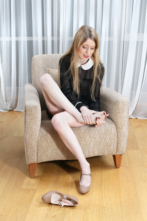 Young woman resting her tired feet on chair after walking on high heels