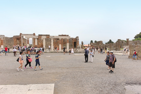 POMPEII, ITALY - June 25; Famous UNESCO heritage antique ruins in Pompeii, Italy - June 25, 2014; Large square with remains of destroyed ancient city Pompeii with tourists walking around