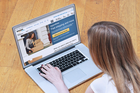 amazon: London, UK - February 06, 2015: Young woman signing up for Amazon Prime on online shopping site. Amazon Prime is paid service that gives Amazon shoppers free delivery and access to Prime Instant Video