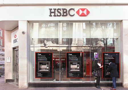 LONDON, UNITED KINGDOM - February 08: HSBC bank branch with glass wall on Oxford Street in London, UK - February 08, 2015; HSBC bank branch with people outside on street using ATM machines