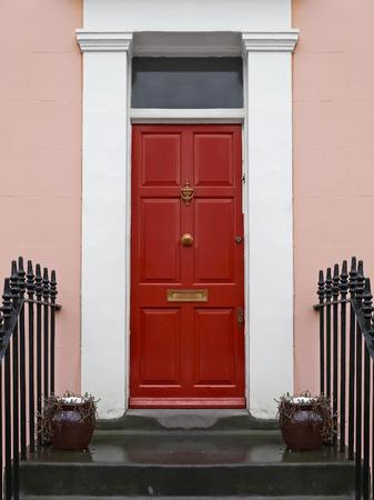 Red entrance front door on old house Standard-Bild