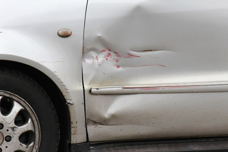 scratches: Red scratch on silver car door exterior