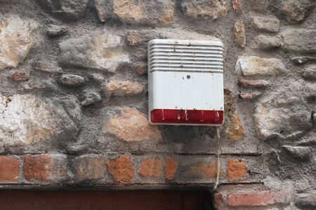 Old dirty burglar alarm on facade of stone house photo