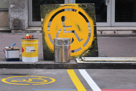 wheelchair access: Fresh yellow paint sign on street for disabled parking space