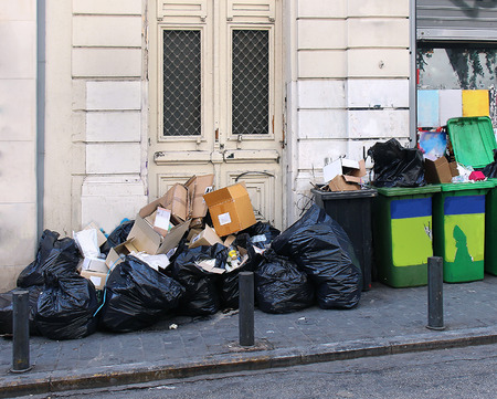 Large garbage pile inside black bags and green containers on street Stock Photo