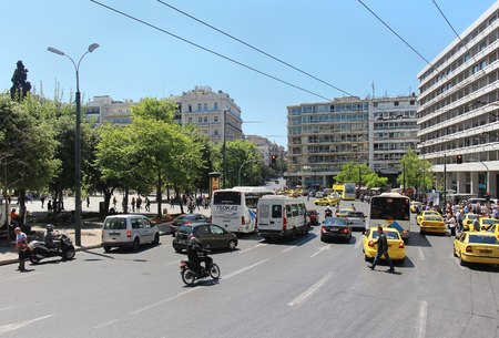 syntagma: ATHENS, GREECE - May 04; Busy street traffic on Syntagma square in Athens, Greece - May 04, 2015; Traffic rush with many yellow cabs and other cars and public transport vehicles making driving difficult and slow.
