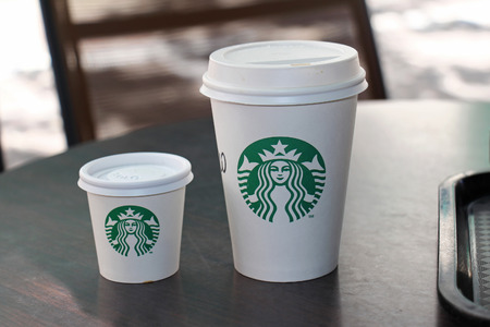 cup coffee: ATHENS, GREECE - MAY 04, 2015: Takeaway hot coffee paper cups at Starbucks store in Athens. Starbucks is an American global coffee company and coffeehouse chain.