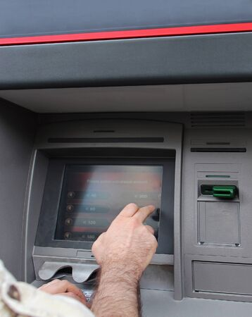 withdraw: Man selecting amount to withdraw from ATM Stock Photo
