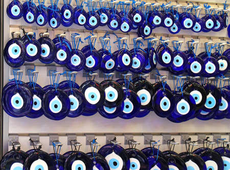 good luck charm: Traditional blue evil eye pendants jewelry hanging on the wall Stock Photo