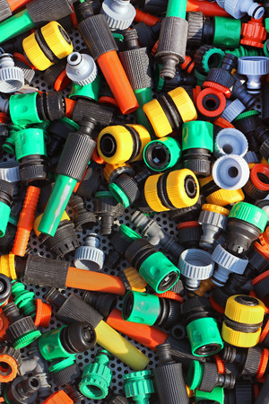 hoses: Colorful plastic pipe fittings pile for gardening hoses