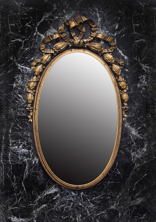 Antique golden frame enchanted mirror on black marble background Archivio Fotografico