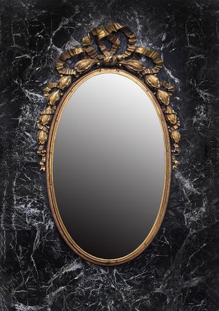 Antique golden frame enchanted mirror on black marble background Standard-Bild