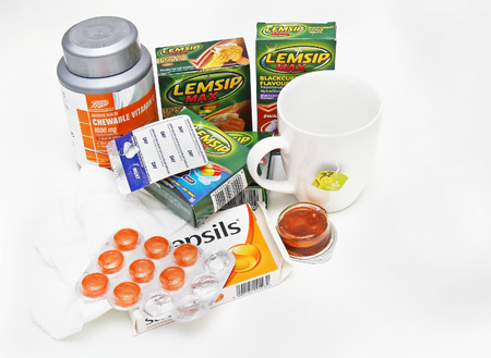 over the counter: LONDON, UNITED KINGDOM - January 19, 2016: Set of over the counter remedies that help with overcoming flu symptoms paracetamol, tea, pastiles and vitamin C