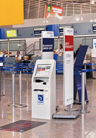 drop off: ATHENS, GREECE - May 05: Baggage drop off and check in at Athens International Airport Eleftherios Venizelos with airport staff behind counters in Athens, Greece - May 05, 2015; Large international airport with passengers walking around in departure hall.