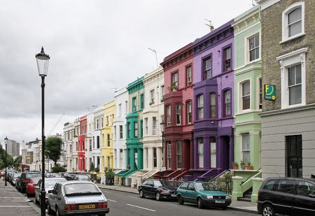 residential: LONDON, UNITED KINGDOM - AUGUST 02: Colorful houses residential street with parked cars in Westminster London, UK - August 02, 2008; Cloudy London street with residential houses and parked cars.