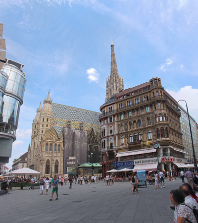 stephansplatz: VIENNA, AUSTRIA - JULY 12; Stephansplatz square with St. Stephen cathedral and tourists walking around in Vienna, Austria - July 12, 2015: Famous historical landmark St. Stephen cathedral during sunny summer day with people walking around in Stephansplatz Editorial