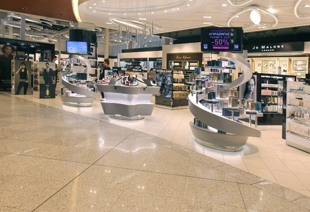 international sales: ATHENS, GREECE - May 05: Duty free shop at Athens International Airport Eleftherios Venizelos with passengers and sales associates walking around in Athens, Greece - May 05, 2015; Duty free shop is popular tax free store where passengers are buying make u Editorial