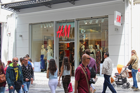 hm: ATHENS, GREECE - May 02; Famous Ermou street shopping district with H&M store and people walking around in Athens, Greece - May 02, 2015; Ermou street is traditional walking street famous for shopping among tourists and locals.