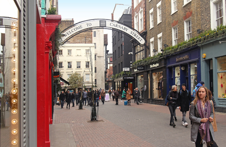 soho: LONDON, UK - March 24: Famous pedestrian shopping street with people walking around on Soho in London, UK - March 24, 2016; Carnaby Street is home to fashion and lifestyle retailers near Regent Street in London.