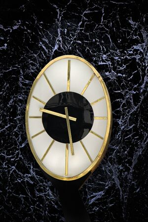 Elegant oval clock with grunge black marble background