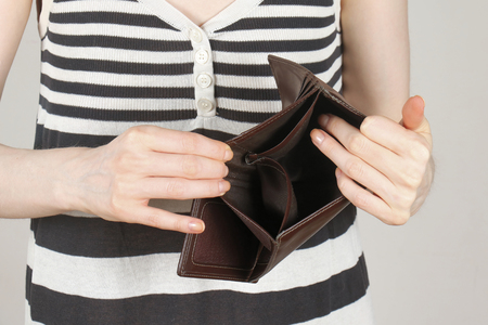 empty wallet: Female showing empty wallet turned upside down