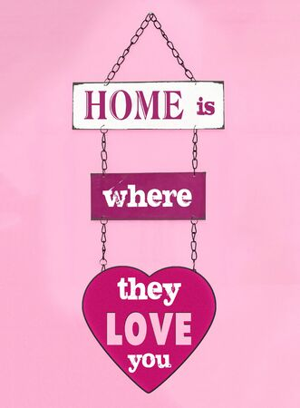 Home is where they live you sign hanging on pink wall Stok Fotoğraf