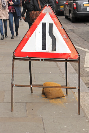 Narrowing street traffic sign on London sidewalk regulating movement of people walking by during works on the road