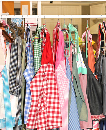 Colorful decorative aprons with retro pattern designs hanging on stander