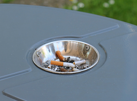 Trash bin full of cigarette butts inside ashtray in public park Reklamní fotografie