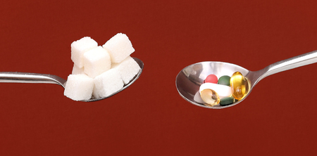 Silver spoons full with white sugar cubes and colorful pills both considered as unhealthy Stock Photo